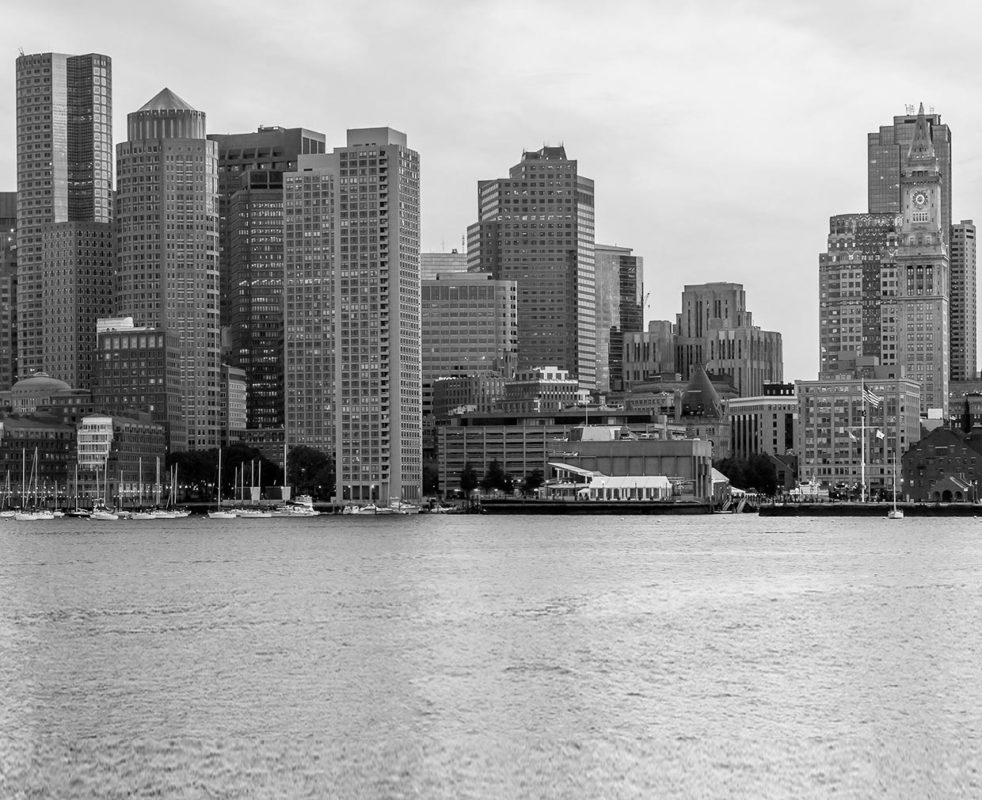 Black and white picture of Downtown Boston with skyscrapers over Boston Harbor