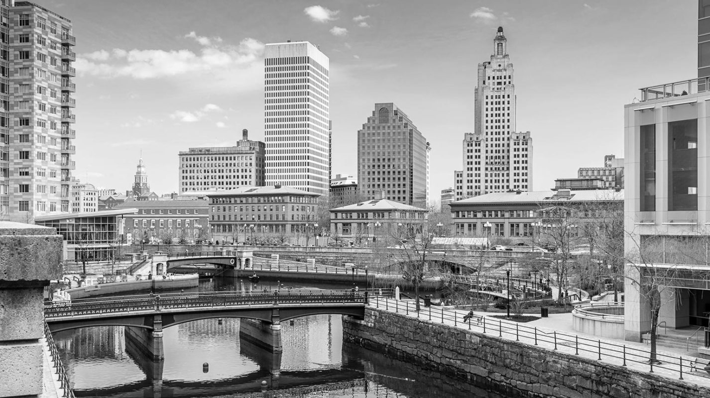Black and white photo of dowtown Providence with skyscrapers overlooking bridge